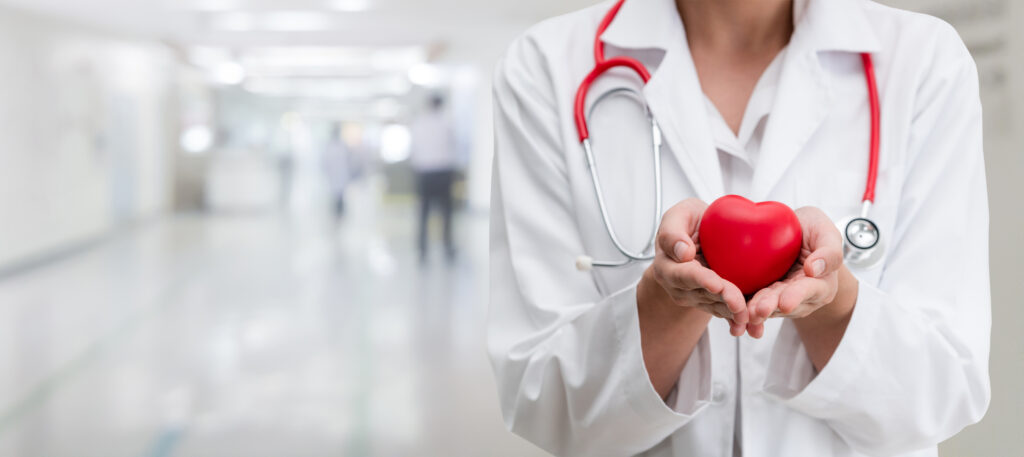 Doctor in a white lab coat with a red stethoscope, standing in hospital corridor holding a red heart